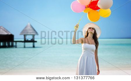 travel, tourism, summer, holidays and people concept - smiling young woman wearing sunglasses with balloons over exotic tropical beach and bungalow background