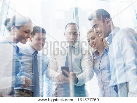 business, teamwork, people and technology concept - business team looking to smartphone in office
