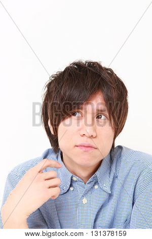 studio shot of young Japanese man worries about something on white background