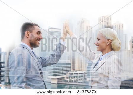 business, partnership, success, gesture and people concept - smiling businessman and businesswoman standing over dubai city background with double exposure effect