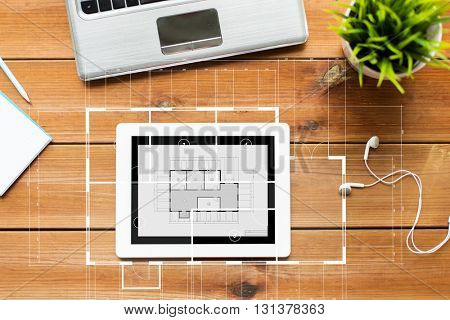 education, business, architecture and technology concept - close up of tablet pc computer, laptop and earphones on wooden table with blueprint projection