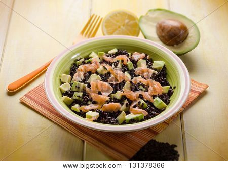 black rice with avocado and smoked salmon, selective focus
