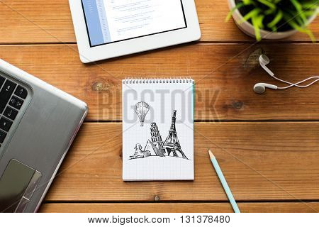 business, tourism, business and technology concept - close up of notebook with landmarks drawing, laptop and tablet pc computer on wooden table