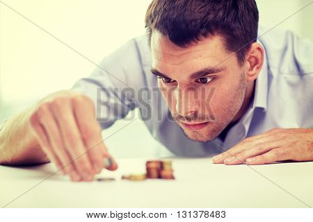 business, people, finances and money saving concept - businessman putting coins into piles at office