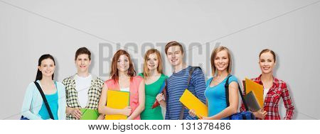 education, school and people concept - group of smiling teenage students with folders and school bags over gray background