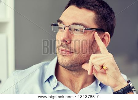 business, people and work concept - portrait of businessman in eyeglasses at office