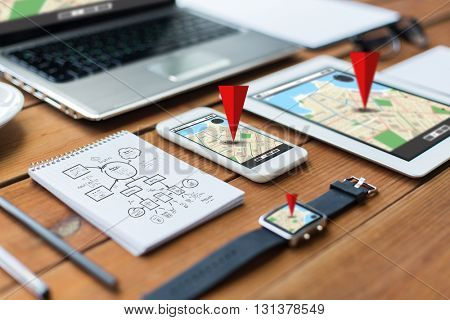 navigation, travel and technology concept - close up of laptop computer, tablet pc, notebook and smartphone with scheme and gps navigator map on wooden table