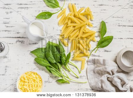 Raw ingredients for making pasta with spinach cream sauce - penne pasta fresh spinach cream cheese and spices on a light wooden background