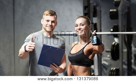 fitness, sport, exercising and diet concept - smiling young woman and personal trainer with clipboard showing thumbs up in gym