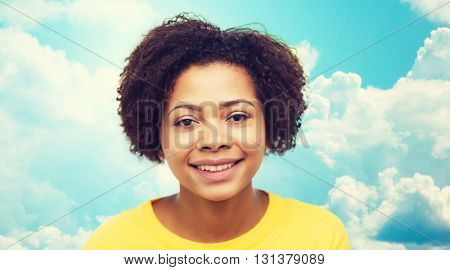 people, race, ethnicity and portrait concept - happy african american young woman face over blue sky with clouds background