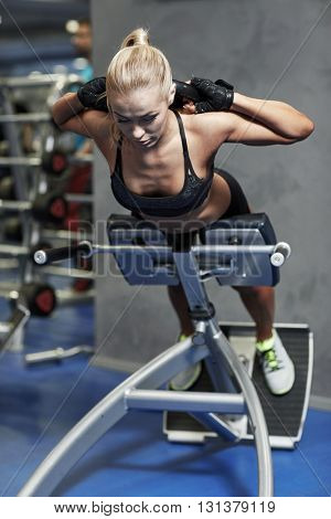 sport, training, fitness, lifestyle and people concept - young woman flexing back and abdominal muscles on bench in gym