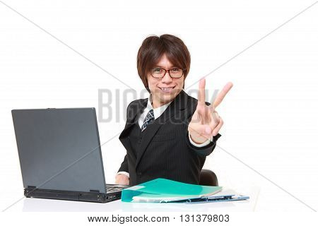 studio shot of young Japanese businessman showing a victory sign on white background