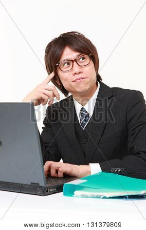 studio shot of young Japanese businessman thinks about something on white background