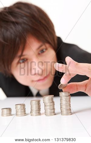 studio shot of Businessman Put Coins To Stack Of Coins on white background