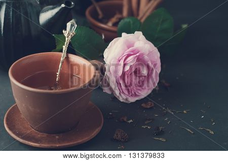 Cup of tea and flowers on black background