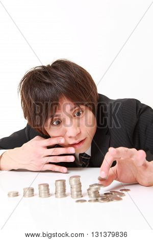 studio shot of stack of coins collapsed when businessman put a coin on white background