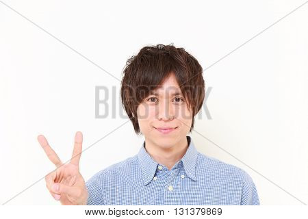 studio shot of young Japanese man showing a victory sign on white background