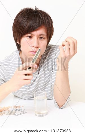 studio shot of young Japanese man suffers from a neurosis on white background