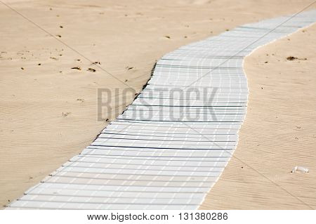 Long white footpath on golden sandy beach