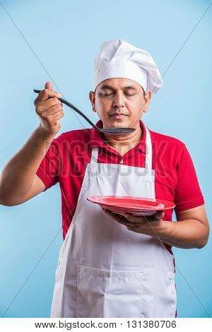 Portrait of an Indian male chef cook holding a red plate and ladle isolated on blue background, asian male chef tasting