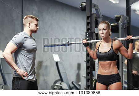 sport, fitness, bodybuilding, lifestyle and people concept - man and woman with barbell flexing muscles in gym