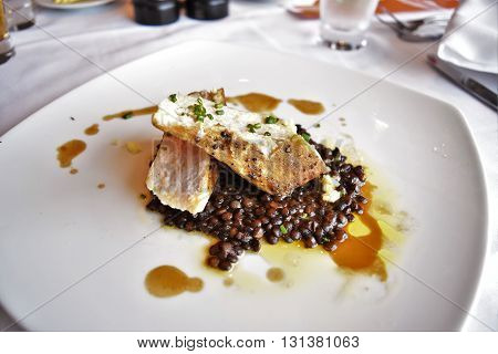 Grilled Swordfish loin with braised lentils and ginger garlic butter.