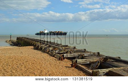 Felixstowe, Suffolk, England - May 03, 2016: A small Container ship entering the Port of Felixstowe being guided by tug, old breakwater in foreground.