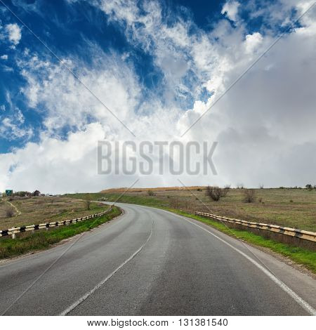 asphalt road to horizon in dramatic sky