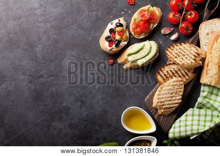 Toast sandwiches with avocado, tomatoes and olives on stone background. Top view with copy space
