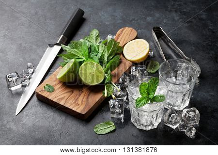 Mojito cocktail making. Mint, lime, ice ingredients and bar utensils