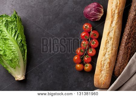 Cooking food ingredients. Lettuce salad, bread and tomato cherry over stone background. Top view with copy space