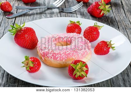 Donut with Strawberry Icing on a white dish with fresh strawberries and dessert forks on the old wooden table close-up macro