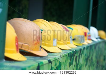 Helmets of builders lying in a one row blur camouflage background