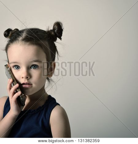 Little girl talking mobile phone. Child using a mobile phone.