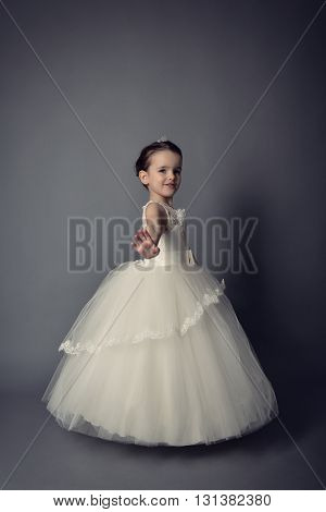 Little Princess posing in evening dress. Little girl dancing ballet in studio over gray background.