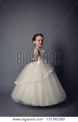 Little Princess posing in evening dress. Little girl dancing ballet in studio over gray background.