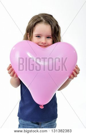 Adorable little girl holding pink balloon heart shaped. Mother's day, valentine's day, love, felling, family concept.