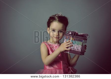 Little Princess holding gift box. Beautiful girl with present. Little lady. Holiday, birthday, New Year, Christmas concept.