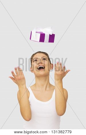 portrait of happy woman thowing up gift