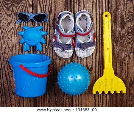Summer accessories of boy on wooden background