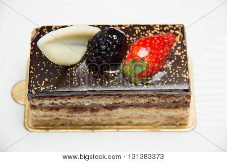 Close up of a A slice of layered chocolate cake topped with a strawberry and blackberry