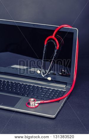 Laptop computer and stethoscope concept, studio shot