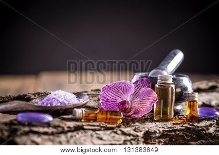Beautiful spa composition with essential oils on wooden background