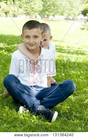 little brother hiding behind his elder brother in the park