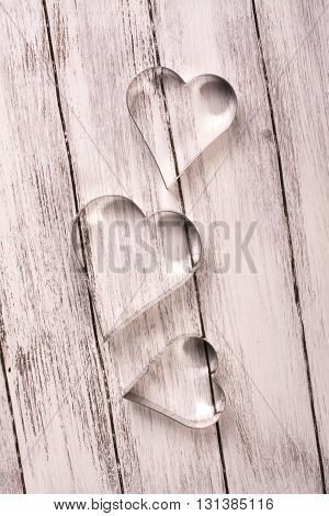 St Valentines Day wooden background with heart shaped cookies cutters