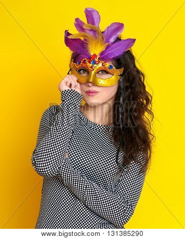 woman in carnival masquerade mask with feather, beautiful girl portrait on yellow color background, long curly hair