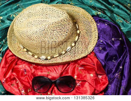 The stylish summer beach accessories. Vacation mood. Straw hat, sunglasses and silk scarf