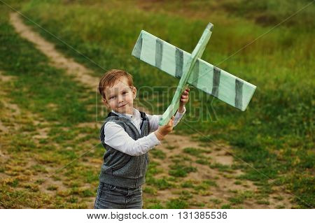 The little boy with the plane outdoors . Game pilot