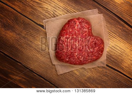 Raw heart shaped burger cutlet over grunge wooden background. Toned image. Top view
