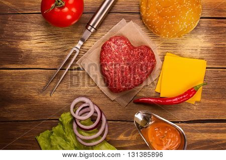 Tasty cheeseburger ingredients over rustic wooden table. Top view